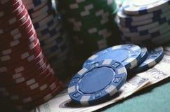 特写镜头堆赌博娱乐场芯片和美金在啤牌桌上 葡萄酒tonned照片 免版税库存照片