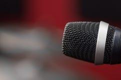 特写镜头黑声音话筒在mic立场,模糊的红色黑暗的bcakground登上了 库存图片