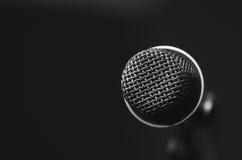 特写镜头黑声音话筒在mic立场,模糊的红色黑暗的bcakground登上了 图库摄影
