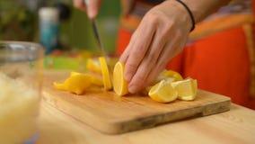 特写镜头女孩切在一个木切板的一个柠檬 影视素材