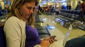 特写镜头女孩同时研究Iphone膝上型计算机在机场 影视素材