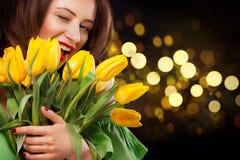 特写镜头女孩画象 微笑与郁金香的美丽的深色的妇女在黑背景的手上开花与bokeh 图库摄影