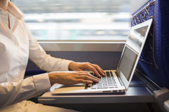 特写镜头妇女递键入在火车的一个膝上型计算机键盘 免版税图库摄影