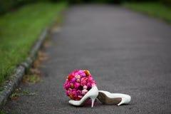 特写镜头射击了典雅的白色婚礼鞋子和新鲜的花束 免版税库存图片