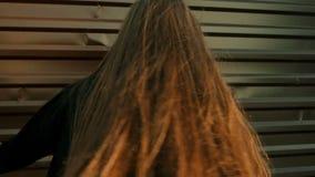 特写镜头射击了在穿灰色开士米夹克的街道的年轻美好的夫人跳舞 股票视频