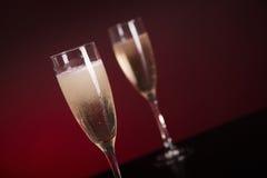 特写镜头射击了在迷人的红色backgrou的两块香槟玻璃 免版税图库摄影