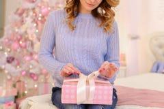 特写镜头射击了妇女有礼物盒的` s手在明亮的卧室w 图库摄影