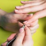 特写镜头射击了接受修指甲的钉子沙龙的一名妇女由有指甲锉的一名美容师 得到钉子修指甲的妇女 Beautici 图库摄影