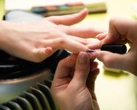 特写镜头射击了接受修指甲的钉子沙龙的一名妇女由有指甲锉的一名美容师 得到钉子修指甲的妇女 Beautici 库存图片