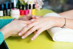 特写镜头射击了接受修指甲的钉子沙龙的一名妇女由有指甲锉的一名美容师 得到钉子修指甲的妇女 库存图片