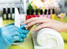 特写镜头射击了接受修指甲的钉子沙龙的一名妇女由有指甲锉的一名美容师 得到钉子修指甲的妇女 免版税库存照片
