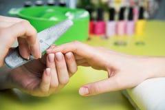 特写镜头射击了接受修指甲的钉子沙龙的一名妇女由有指甲锉的一名美容师 得到钉子修指甲的妇女 免版税图库摄影