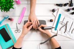 特写镜头射击了接受修指甲的钉子沙龙的一名妇女由有指甲锉的一名美容师 得到钉子修指甲的妇女 免版税库存图片
