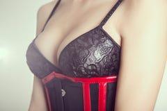 特写镜头射击了黑胸罩和束腰的一名大乳房妇女 图库摄影