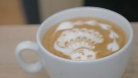特写镜头射击了barista精整在拿铁matcha的奶油图片 股票录像
