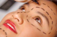 特写镜头少妇面对为与在皮肤画的线的整容外科做准备,测量的医生使用红色工具,  免版税图库摄影