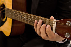 特写镜头弹吉他的一套黑衣服的一个年轻人 免版税库存照片