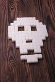 特写镜头形成头骨的糖立方体 在棕色背景的被提炼的白糖 糖替补 糖尿病概念 库存照片