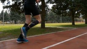 特写镜头慢动作射击了跑步在路线轨道的一个人腿 股票录像