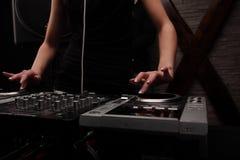 特写镜头手 妇女在有演奏在搅拌器的白色耳机的黑人dj音乐与光束作用 库存照片