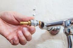 特写镜头手水管工安装轻拍阀门到厨房水龙头 库存图片