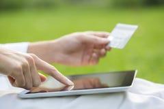 特写镜头拿着信用卡和使用片剂个人计算机的妇女的手 免版税图库摄影