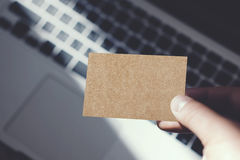特写镜头显示空白的工艺名片和使用现代膝上型计算机被弄脏的背景的图象人 大模型准备好私有 免版税库存照片