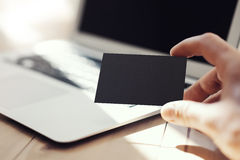 特写镜头显示空白的黑名片和使用现代膝上型计算机木头表的照片人 被弄脏的背景 准备好的大模型 免版税图库摄影