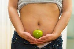 特写镜头有拉开拉链的牛仔裤和衬衣的妇女胃提起了,拿着在手之间的苹果,可看见的内衣 库存照片