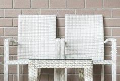 特写镜头木织法桌和木头编织在被弄脏的棕色砖墙纹理背景,在放松的美好的内部的椅子  免版税库存图片