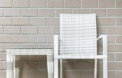 特写镜头木织法桌和木头编织在被弄脏的棕色砖墙纹理背景,在放松的美好的内部的椅子  图库摄影