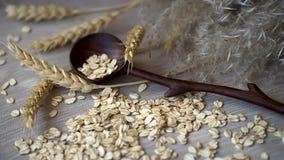 特写镜头未加工的燕麦剥落与木匙子和不同的耳朵反对一张简单的粗糙的亚麻布餐巾 概念  库存图片