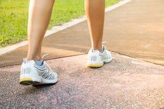 特写镜头概念英尺健身凹凸部跑腿者跑鞋日出健康妇女锻炼 库存照片