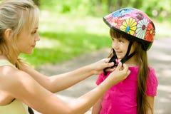 特写镜头年轻母亲穿戴她的女儿的自行车盔甲 免版税库存图片