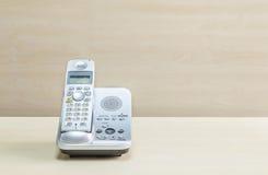 特写镜头灰色电话、办公室电话在被弄脏的木书桌上和墙壁构造了背景在会议室在窗口光下 免版税图库摄影