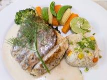 特写镜头烤鲈鱼牛排服务用白葡萄酒调味汁、炒饭用黄油和煮熟的菜在白色板材 免版税库存图片