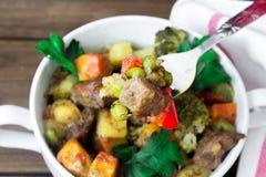 特写镜头牛肉肉炖了与在陶瓷罐的菜有在一把叉子的一个片断的在木背景 免版税库存图片