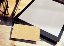 特写镜头现代片剂空白白色屏幕,在内部Coworking演播室地方里面的玻璃木表 空的大模型设计 库存图片