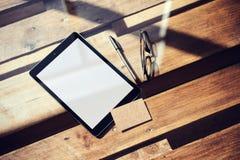 特写镜头现代片剂空白白色屏幕,在内部Coworking演播室里面的玻璃木表 空的大模型设计卡拉服特 图库摄影
