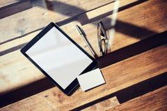 特写镜头现代片剂空白白色屏幕,在内部Coworking里面的玻璃木表 空的显示,清楚大模型的设计 库存图片