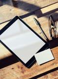特写镜头现代片剂空白白色屏幕,在内部Coworking顶楼里面的玻璃木表 清楚空的大模型的设计 图库摄影