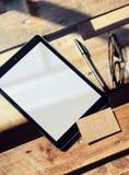 特写镜头现代片剂空白白色屏幕,在内部Coworking顶楼里面的玻璃木表 空的大模型设计卡拉服特 图库摄影