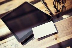 特写镜头现代片剂空白黑色屏幕,在内部Coworking演播室地方里面的玻璃木表 空的大模型设计 库存照片