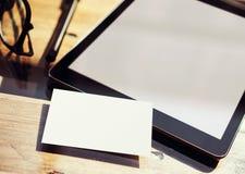 特写镜头现代片剂黑屏,在内部Coworking演播室地方里面的玻璃木表 空的大模型设计白色 库存图片