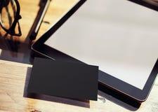 特写镜头现代片剂黑屏,在内部Coworking演播室地方里面的玻璃木表 空的大模型设计黑色 图库摄影