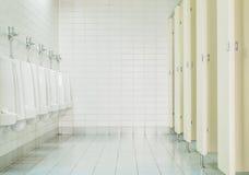 特写镜头由尿壶和小室铺磁砖在人洗手间的墙壁有洗手间视图,内部在老洗手间背景 免版税库存图片
