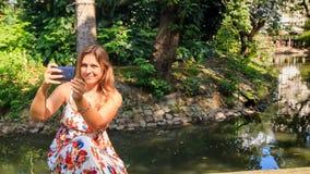 特写镜头白肤金发的女孩做Selfie反对小河在公园 影视素材