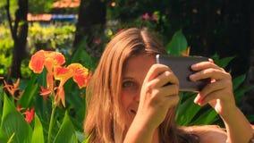 特写镜头白肤金发的女孩做Selfie反对花在公园 影视素材