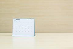 特写镜头白色日历在被弄脏的木书桌和墙壁上的7月构造了背景在会议室在窗口光下 库存照片
