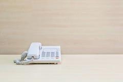 特写镜头白色电话、办公室电话在被弄脏的木书桌上和墙壁构造了背景在会议室在窗口光下 免版税库存照片